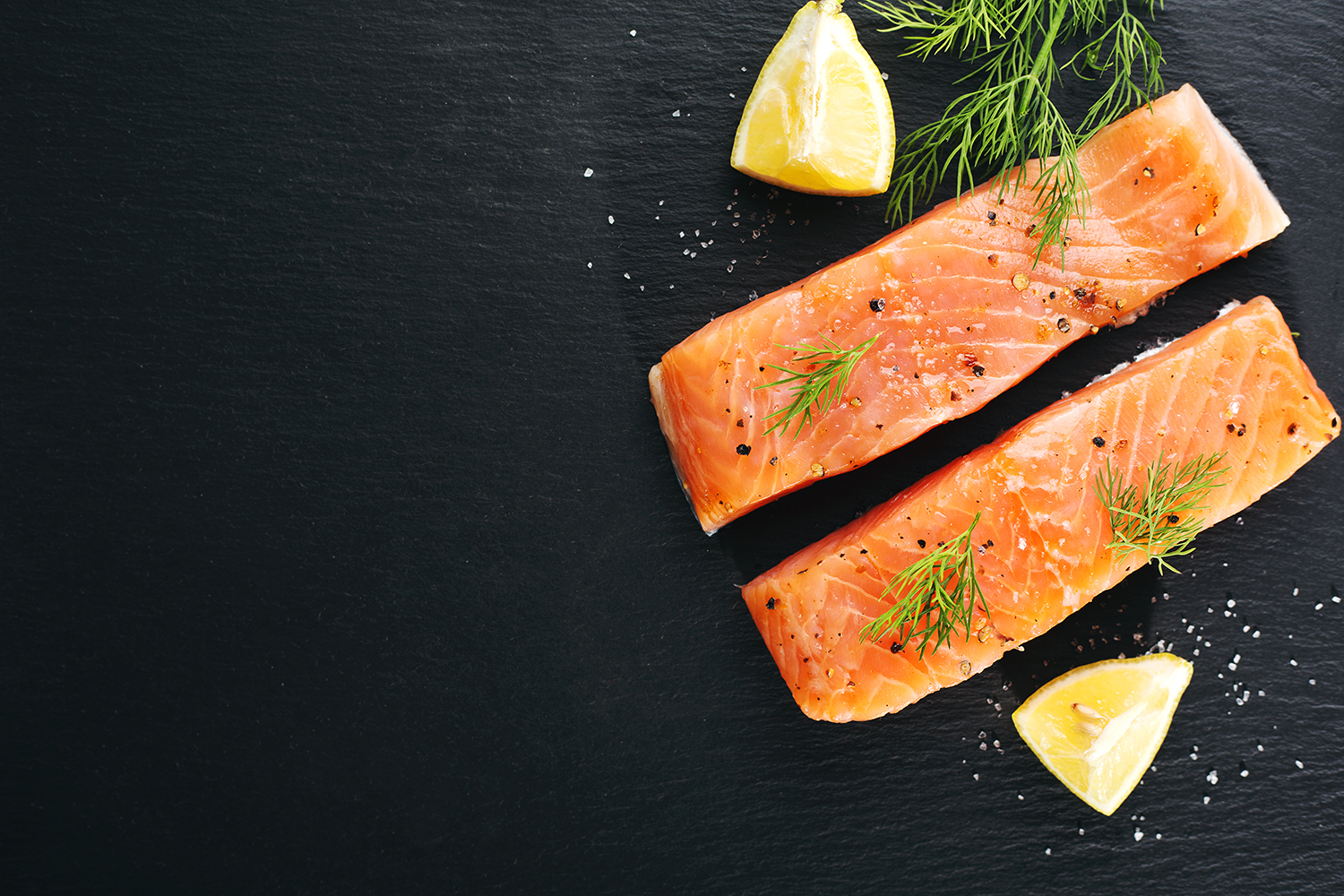 Raw Fresh Tasty Salmon Steaks Placed On Black Slate With Ingredients. Ready To Cook. Slate Background. Horizontal With Copy Space